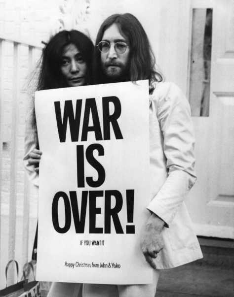 John Lennon (1940 - 1980) and Yoko Ono pose on the steps of the Apple building in London, holding one of the posters that they distributed to the world's major cities as part of a peace campaign protesting against the Vietnam War. 'War Is Over, If You Want It'.   (Photo by Frank Barratt/Getty Images)