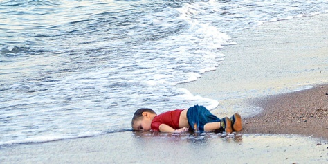 FILE - In this Sept. 2, 2015 file photo, a paramilitary police officer investigates the scene before carrying the lifeless body of Aylan Kurdi, 3, after a number of migrants died and others were reported missing when boats carrying them to the Greek island of Kos capsized near the Turkish resort of Bodrum. The tides also washed up the bodies of the boy's 5-year-old brother Ghalib and their mother Rehan on Turkey's Bodrum peninsula. Their father, Abdullah, survived the tragedy. (AP Photo/DHA, File) TURKEY OUT